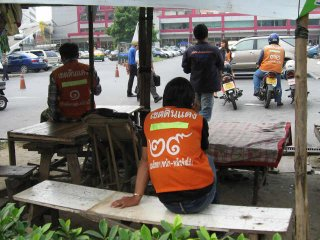 Thajské číslice na zádech taxíkářů